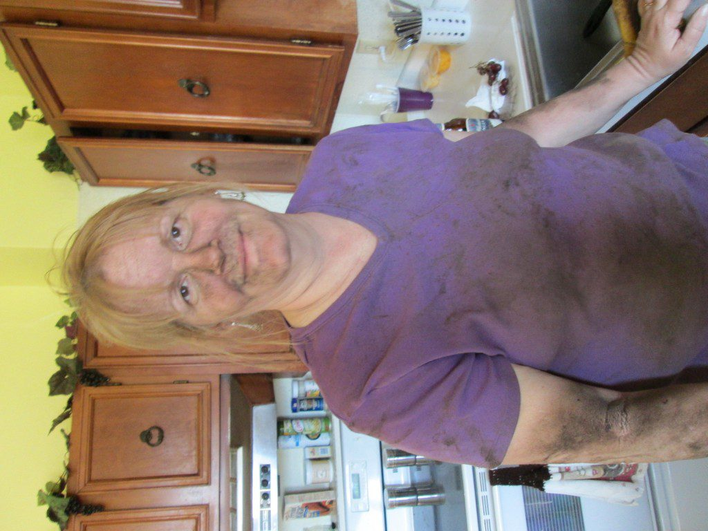 This is my mom about half-way through scraping all the crud off the bottom of said tractor... I think she looks great!  Should have seen her at the end of it... haha. Though I gave her a hard time for not wearing a mask...